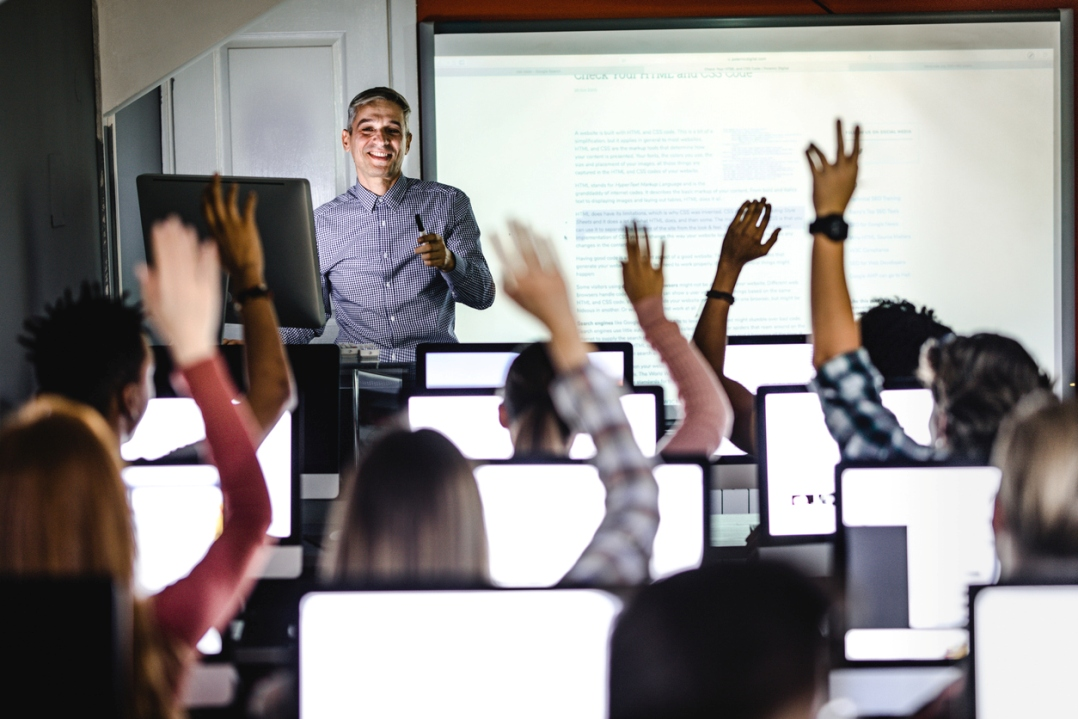 Trainer and telephone reps at computers, raising their hands in a class