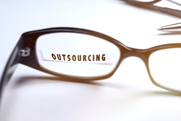 "The word, ""Outsourcing,"" magnified through reading glasses on table"