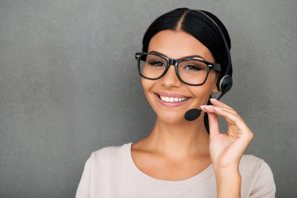 Telephone sales rep wearing headset and smiling